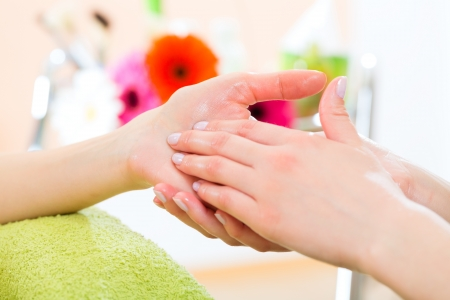 hands massage: Woman in a nail salon receiving a manicure by a beautician, she is getting a hand massage