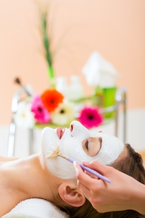 nurturing: Wellness - woman receiving nurturing facial mask in spa for moist and clean skin