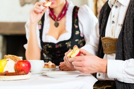 trachten: Couple in a traditional mountain hut having a meal