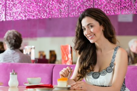 Young woman in a cafe or ice cream parlor eating a cake, maybe she is single or waiting for someone photo