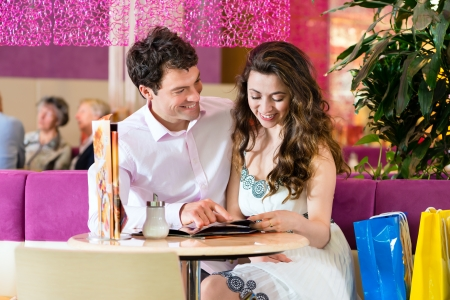 Young Couple in a Cafe or Ice cream parlor, she showing something in a bag Stock Photo - 22046460