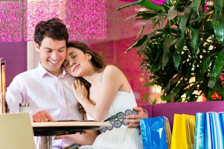 Young Couple in a Cafe or Ice cream parlor, she showing something in a bag photo