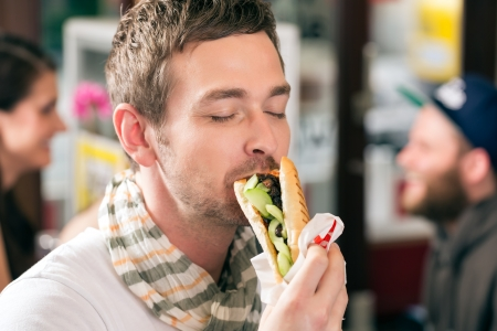 Hotdog - young customer in a snack bar eating delicious fast food sausages photo