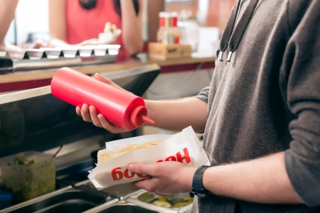 concession: Hotdog - friendly salesman and fresh ingredients in a fast food snack bar Stock Photo