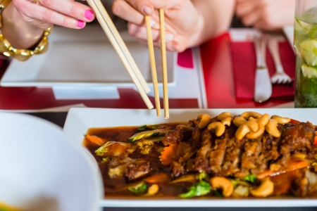 Young people eating in a Thai restaurant, they eating with chopsticks, close-up on hands and food photo