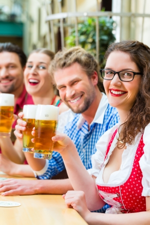 tracht: Friends in traditional Bavarian Tracht in restaurant or pub with beer in Bavaria, Germany