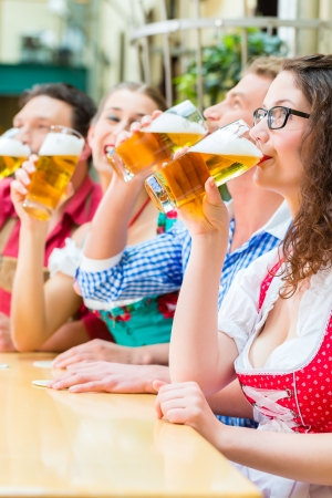 Friends in traditional Bavarian Tracht in restaurant or pub with beer in Bavaria, Germany photo