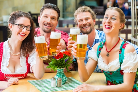 tracht: Friends in traditional Bavarian Tracht in restaurant or pub drinking beer in Bavaria, Germany