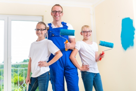 Father and his daughters or daughter with her friend are painting with paint roller a wall in blue.