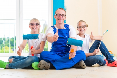 redesign: Father and his daughters or daughter with her friend are painting with paint roller a wall in blue.