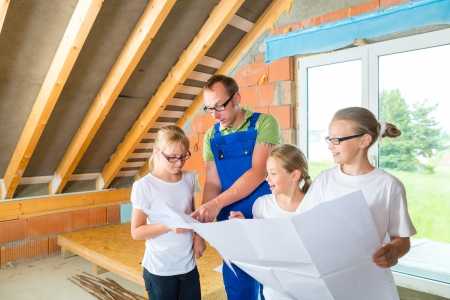 Father and kids or daughters and friends looking at a construction plan on a building site photo