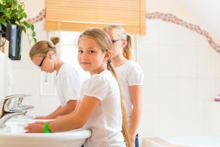 pijamada: Los niños - hermanas o hijas con sus amigos se están lavando las manos en el lavabo