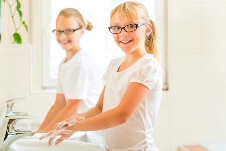 lavandose las manos: Los niños - hermanas o hijas con sus amigos se están lavando las manos en el lavabo
