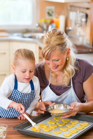 cookie sheet: Baking with the family - Mother and daughter coat self made cookies with a brush