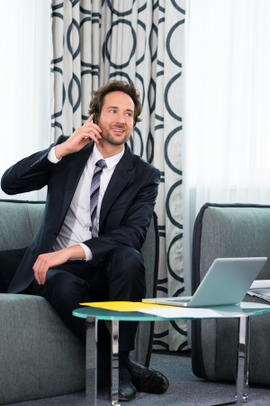 Businessman working in business hotel, he discusses some documents with a customer on the phone Stock Photo - 22046748