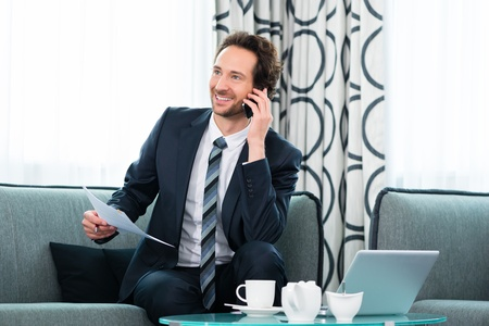 Businessman working in business hotel, he discusses some documents with a customer on the phone Stock Photo - 22046751