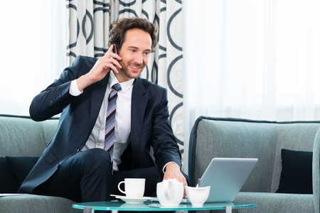 Businessman working in business hotel, he discusses some documents with a customer on the phone Stock Photo - 22046752