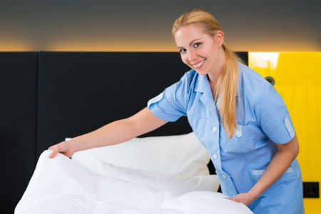 Hotel Room service - young chambermaid changing the bedding or bedclothes in a room photo