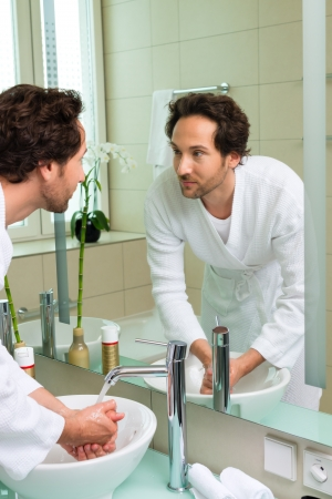 Young man in the hotel bathroom, suite, refreshing himself and washing the face at the sink Stock Photo - 22047003