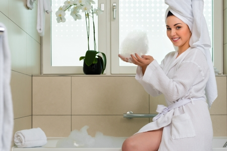 Young woman in bathroom of hotel making a bubble bath photo