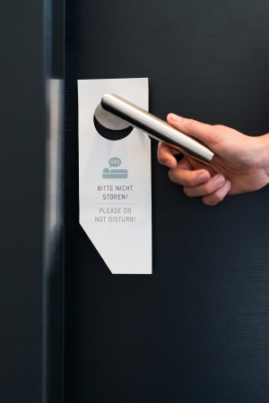 Hotel room service - someone ignores the please do not disturb sign on handle on door of suite in hotel