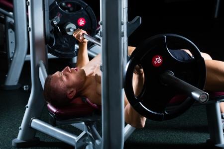 hombre fuerte: Hombre fuerte - culturista con pesas en un gimnasio, hacer ejercicio con una mancuerna Foto de archivo