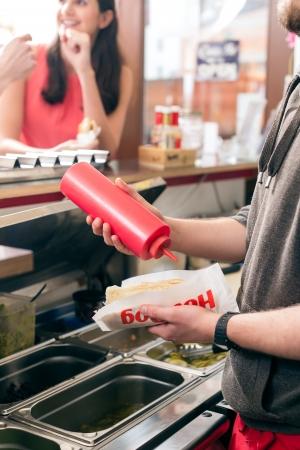Hotdog - vriendelijke verkoper en verse ingrediënten in een fast food snackbar Stockfoto