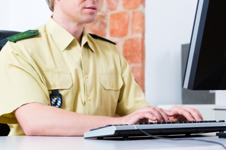 constable: Police officer in police department working on the computer, on a case or registering a complaint