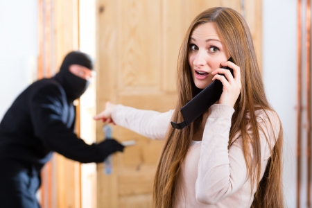 llamando: Seguridad - romper ladrón disfrazado en un apartamento u oficina, una mujer llamando a la policía con su teléfono o teléfono