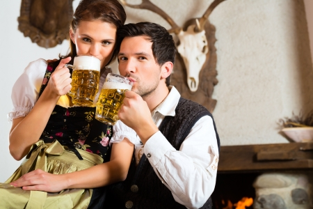 trachten: Couple in a traditional mountain hut with fireplace drinking beer