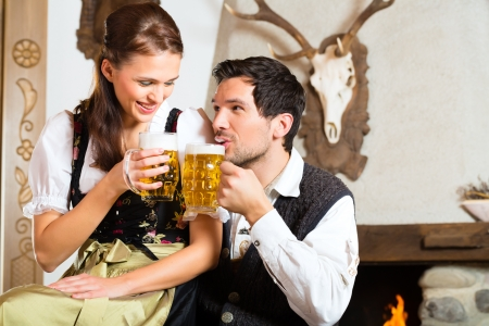 Couple in a traditional mountain hut with fireplace drinking beer photo