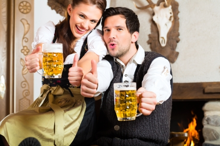 Couple in a traditional mountain hut with fireplace drinking beer Stock Photo - 22027223