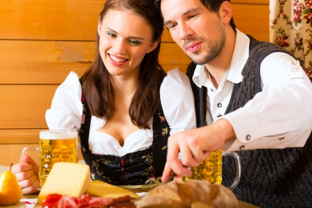 trachten: Couple in a traditional mountain hut having a meal with bread and cold cuts