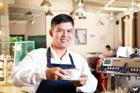 Coffeeshop - asian barista presents coffee in his shop photo