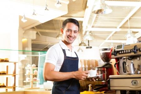 coffeeshop: Coffeeshop - asian barista presents coffee in his shop