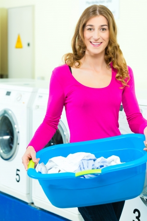 launderette: Young woman with laundry basket in a laundrette she washed their laundry clean and is happy about it