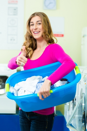 Young woman with laundry basket in a laundrette she washed their laundry clean and is happy about it Stock Photo - 22041737