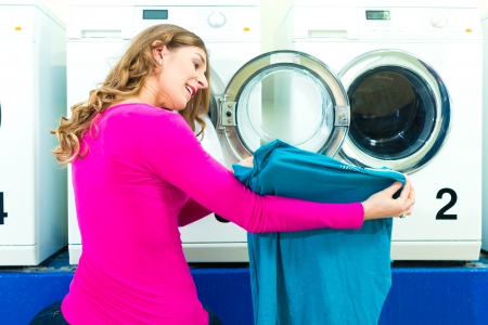 launderette: Woman in a launderette, washing her dirty laundry, in the background are washing machines, a female student is pleased about her clean blouse Stock Photo