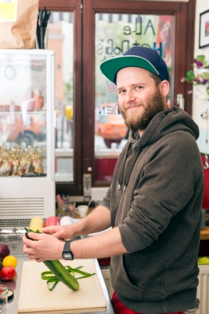 casse-cro�te: Hotdog - Chef amical pr�paration des ingr�dients frais dans un rapide casse-cro�te de nourriture