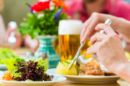 Young people in traditional Bavarian Tracht eating pork in restaurant or pub for lunch or dinner Фото со стока