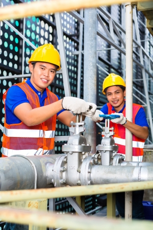 Two technicians or engineers working on a valve on building technical equipment or industrial site Stock Photo - 22042080