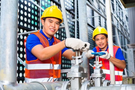 tallyman: Two technicians or engineers working on a valve on building technical equipment or industrial site