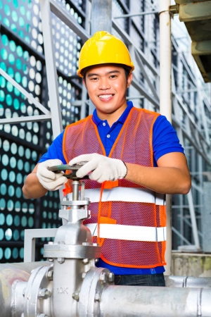 technician or engineer working on a valve on building technical equipment or industrial site  photo
