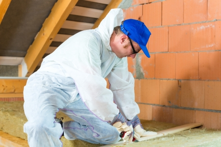Worker in overall is cutting insulating material with gloves and knife  Stock Photo