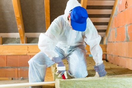 house renovation: Worker in overall is cutting insulating material with gloves and knife  Stock Photo