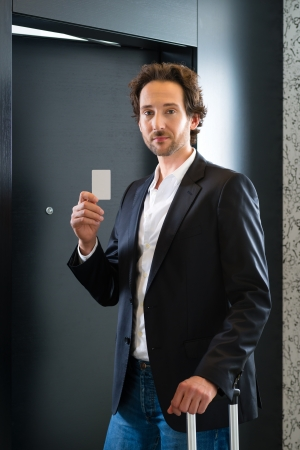 Young business man standing with a keycard in front of a room door in a hotel Stock Photo - 22042090