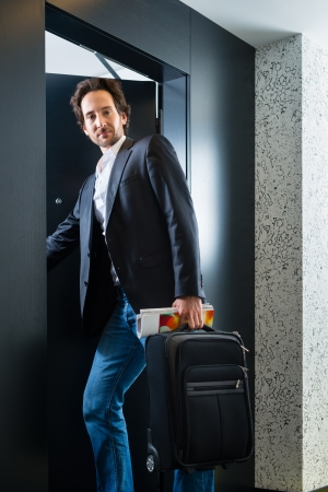 hotel suite: Young man standing with a trolley in front of a room door in a hotel Stock Photo