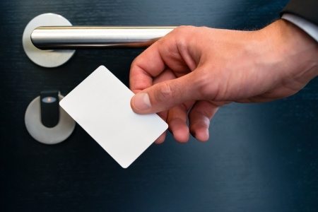 hotel door: Hotel door - Young man holding a keycard in front of the electronic sensor of a room door  Stock Photo