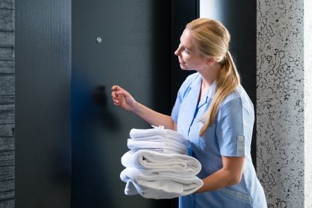 woman in towel: Hotel room service - young chambermaid standing in front of a room door in a suite with fresh towels