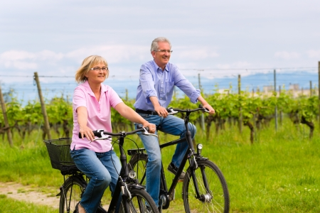 Senior Man and woman exercising with bicycles outdoors, they are a couple Stock Photo - 22042184